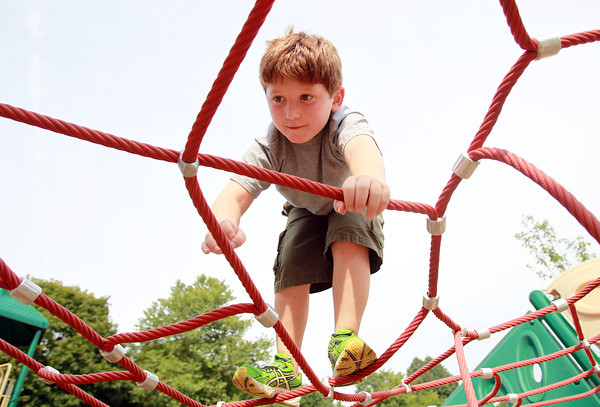 Beverly: Gavin Ferretti, 7, of Beverly, carefully scales his way across a rope spiders web at Kimball Haskell Park in Beverly on Tuesday afternoon. David Le/Salem News