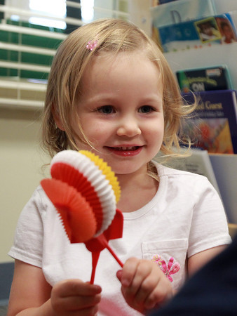 Peabody: Three-year-old Izzy Brown proudly shows off the flower she made from a toy brought by Aviv Living Center resident Marty Lawson, who throughout the year brought toys and gadgets for the students to play with. David Le/Salem News