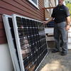 Salem:<br /> Rep. John Keenan examines solar panels that are to be installed on his roof.<br /> Photo by Ken Yuszkus, The Salem News, Friday, August 16, 2013.