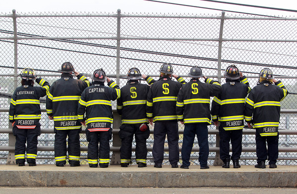 Peabody: Firefighters from Salem, Peabody, and Cambridge stood together on the Farm Ave overpass over Rt-95 South and saluted as the funeral procession of former Salem firefighter Kevin O'Boyle passes underneath. O'Boyle was a member of the Salem Fire Department for over 5 years and this past summer started working for the Cambridge Fire Department. David Le/Salem News