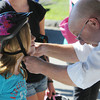 Beverly:<br /> Olivia Wheeler, 7, received her new safety helmet which was adjusted by Kiwanis member Bob Mitchell at the kids bike safety rodeo at Lynch Park. An age-appropriate obstacle course was constructed and directed by officers of the Beverly Police Department. Members of the Kiwanis Club of Beverly offered safety information and provide a helmet for all children in need of one.  <br /> Photo by Ken Yuszkus, Salem News , Monday, August 5, 2013.
