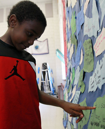 """Salem: Joshua Giaff-Hodge, 6, a participant in the Bentley Elementary School's summer Science and Reading program, reads his learning goal posted on the """"Wave of Learning"""" on Thursday morning. David Le/Salem News"""