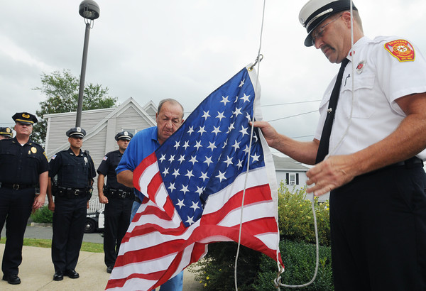 Danvers:<br /> Jim George, left, helps Danvers Fire Captain James Brooks attach the flag which flew over Afghanistan to the rope to be raised up the flag pole at the Danvers Fire Department.<br /> Photo by Ken Yuszkus, Salem News, Thursday, August 8, 2013