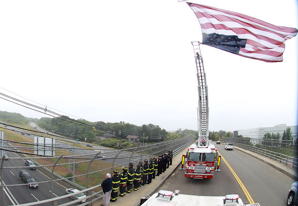 Peabody: Firefighters from Salem, Peabody, and Cambridge stood together on the Farm Ave overpass over Rt-95 South and saluted as the funeral procession of former Salem firefighter Kevin O'Boyle passes underneath. O'Boyle was a member of the Salem Fire Department for over 5 years and this past summer started working for the Cambridge Fire Department. A large American flag was draped between a Salem and Cambridge ladder trucks to honor the fallen firefighter. David Le/Salem News