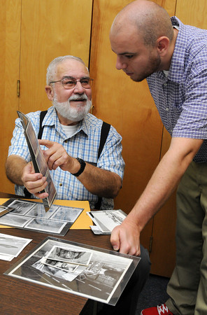 Beverly:<br /> Rob Goodwin, left, shows photos to Jon Shields before they are scanned at the The Salem News. Rob served in Korea and Vietnam. North of Boston Media Group is gathering photos of veterans of war for a collector's edition coffee-table book to be be out in December. For information on how to purchase a book, see our ad PAGE ##, or visit WEBSITE.<br /> Photo by Ken Yuszkus, Salem News, Monday, August 12, 2013.