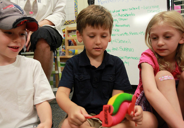 Peabody: From left, Aidan Brown, Ben Beader, and Samantha Kaplan, all 5, play with a paper flower toy brought by Aviv Living Center resident Marty Lawson. Throughout the year Lawson, a resident at the Aviv Living Center, visited the classroom and brought along toys and gadgets for the students to play with. David Le/Salem News