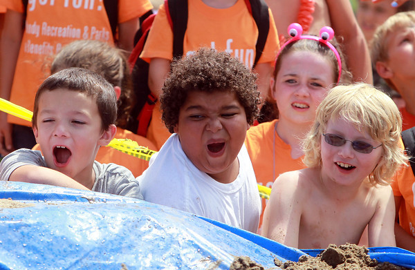 Beverly: From left, Beverly Recreation Department campers Nate Martin, 9, Caleb Kane, 10, and Aidan Lonegan, 10, react as counselors put on a mud wrestling show for campers from the Beverly and Peabody Rec Departments during their annual Luau at Lynch Park on Thursday afternoon. David Le/Salem News
