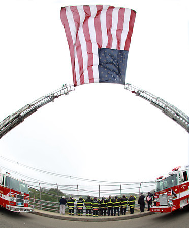 Peabody: With an American flag flying between Salem and Cambridge ladder trucks, firefighters from Salem, Peabody, and Cambridge stood together on the Farm Ave overpass over Rt-95 South and saluted as the funeral procession of former Salem firefighter Kevin O'Boyle passes underneath. O'Boyle was a member of the Salem Fire Department for over 5 years and this past summer started working for the Cambridge Fire Department. David Le/Salem News