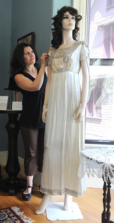 """Peabody:<br /> Curator Heather Leavell adjusts the sleeve on the revival style dress of the Napolean era from 1910 on display at the """"Downton Abbey Style,"""" exhibit showing clothing from the Downtown Abbey era -- World War I to the Jazz Age at the Peabody Historical Society.<br /> Photo by Ken Yuszkus, The Salem News, Friday, August 16, 2013."""