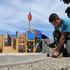 Hamilton:<br /> Julio Pereira DeMoura works on the transitional edge where foam matting will meet the cement sidewalk at the new playground in Patton Park. <br /> Photo by Ken Yuszkus, Salem News, Wednesday, August 7, 2013.