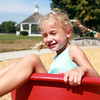 Hamilton: Julia Bissett, 4, of Beverly, laughs as she whirls around on a spinning bucket seat at the new Patton Park Playground on Wednesday afternoon. David Le/Salem News