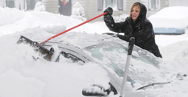 Beverly: Nancy Hayes uses a broom to clean off her cars during the snowstorm on Monday morning.<br /> Photo by Ken Yuszkus/Salem,  News, Monday,  December 27, 2010.