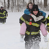 Firefighter Mike Zarbano carries one of the two girls rescued from a brook at the Beverly Golf & Tennis Club yesterday afternoon. Firefighter Dave Mirandi is on the right. In the background on a sled being pulled by other firefighters is the other girl who was rescued. The other firefighters are Bob Atherton, Derek Belanger and Peter Davis. Photo by Ken Yuszkus/Salem,  News, Monday,  December 27, 2010.
