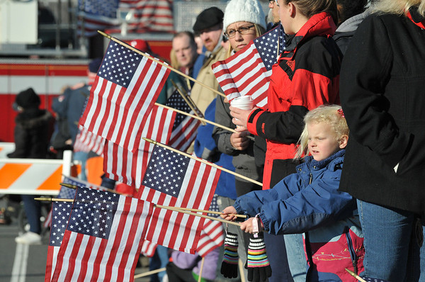 Samantha Chasse, 5, of Salem holds a flag along the procession route.   photo by Mark Teiwes / Salem News
