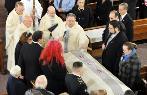 At the beginning of a funeral for of U.S. Sgt. James Ayube Jr. of Salem, a combat medic killed last week in Afghanistan, the Rev. John Sheridan, Paster of St. James Church, center, gives a blessing at the casket with Ayube's family gathered around.   photo by Mark Teiwes / Salem News