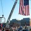 A motorcade for the funeral of U.S. Sgt. James Ayube Jr. of Salem Massachusetts, a combat medic killed last week in Afghanistan, passes by a flag held by two fire truck ladders on North Street in Salem.   photo by Mark Teiwes / Salem News