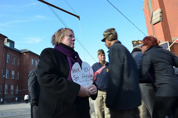 Kathy Robbins of Beverly holds a sign at the funeral for U.S. Sgt. James Ayube Jr.   photo by Mark Teiwes / Salem News