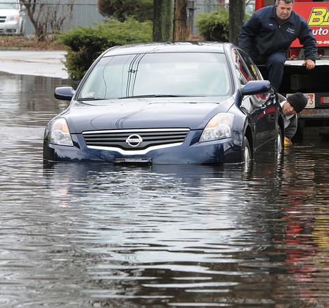 Peabody: Tow truck operators prepare to remove one of the two abandoned cars that were stranded in the high water on Railroad Avenue created by the heavy rainfall. Photo by Ken Yuszkus/Salem News, Wednesday, March 31, 2010.