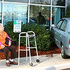 "Eleanor Curr, 73, of Peabody sits next to her car, which crashed into the side of an office building at the Cummings Center in Beverly on March 18. She and her husband, William, were on their way to a medical appointment when she became distracted. ""I must have stepped on the gas instead of the brake,"" she said. No one was hurt. That is her husband's walker next to her. Photo by Mark Lorenz/Salem News"