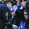 At the burial of U.S. Sgt. James Ayube Jr. of Salem Massachusetts, a combat medic killed in Afghanistan, Lauren Ayube, James' widow, center, and James' parents Christina and James Sr. receive flags at the Harmony Grove Cemetery.   Photo by Mark Teiwes / Salem News. Dec, 18, 2010