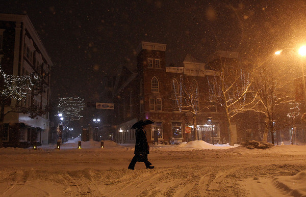 Salem: A man trudges along Washington St in Salem using an umbrella to shield the howling wind and snow on Tuesday evening. DAVID LE/Staff Photo