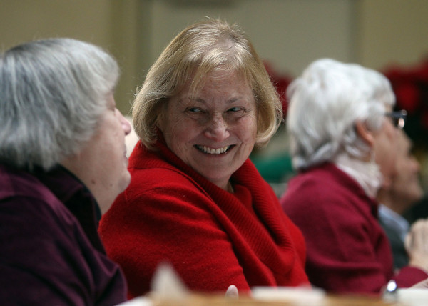 Danvers: Deenie Porter, right, of Beverly, smiles while chatting with Betty Gray, of Hamilton, at the 32nd annual Christmas Dinner with Friends held at the North Shore Unitarian Universalist Church in Danvers on Wednesday afternoon. DAVID LE/Staff Photo