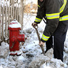 Ken Yuszkus/Staff photo: Beverly: Beverly Fire Captain Kevin Smith clears the snow around a firehydrant on Brimbal Avenue at the corner of Colon Street. Firefighters were clearing around hydrants because the upcoming snow storm is expected to dump 2-4 inches of more snow.