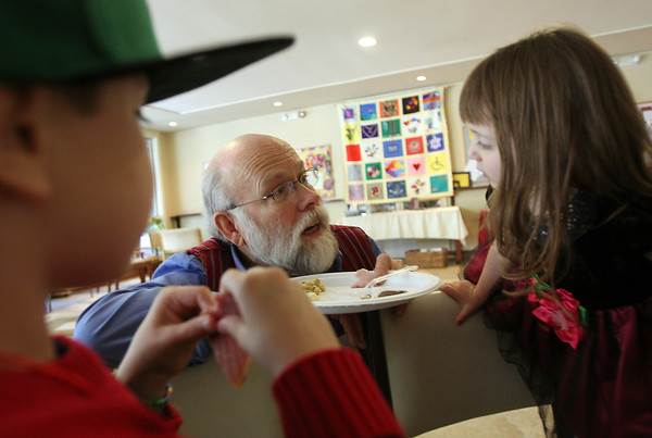 Danvers: Bob Ferris, center, talks with his grandchildren Matthew Ferris, 6, left, and Olivia Ferris, 2, at the 32nd annual Christmas Dinner with Friends held at the North Shore Unitarian Universalist Church in Danvers on Wednesday afternoon. DAVID LE/Staff Photo