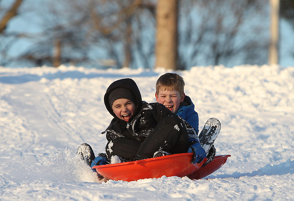 Beverly: Thomas Herrick, 8, left, and Thomas Beasley, 9, right, let out shouts of excitement as they barrel down the hill at Lynch Park in Beverly on Wednesday afternoon. DAVID LE/Staff Photo