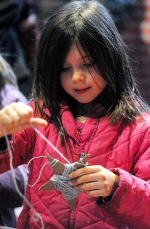 Ken Yuszkus/Staff photo: Ipswich: Madeline Wood, 6, of Wenham, winds yarn around her star decoration at Appleton Farms in Ipswich. Many people attended a family holiday event centered around the Nisse, an elf-like creature who lives in the arns and protects the farmers, animals and crops.