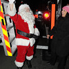Ken Yuszkus/Staff photo. Salem: Santa arrives. He just climbed down from the Salem Fire Department's new ladder truck and the Mayor Kim Driscoll is there to welcome him before he makes his way through the crowd to get to the tree lighting in Salem Common.
