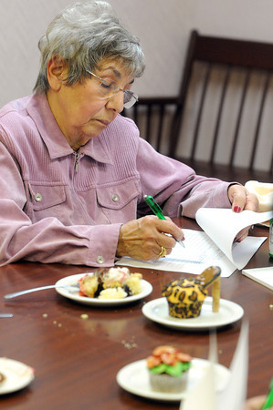 Ken Yuszkus/Staff photo: Peabody: Mary Ann Juliano rates a cupcake. She is one of a panel of 4 judges that judged cupcakes based on several categories at the Peabody Glen Health Care Center.