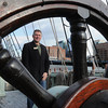 Ken Yuszkus/Staff photo: Swampscott resident Shawn Ford is seen through the wheel of the ship Eleanor which is tied up at the Boston Tea Party Ships and Museum.