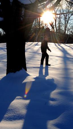 Ken Yuszkus/Staff photo: Danvers: Park Ranger Tyler Berry walks through the snow amongst the long winter shadows at Endicott Park in Danvers.