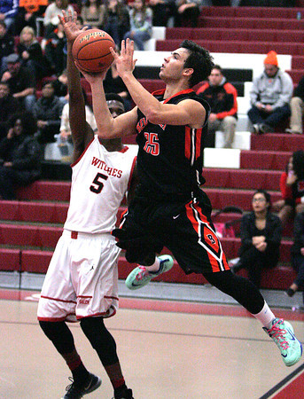 Ken Yuszkus/Staff photo: Salem:<br /> Beverly's Jonathan Berchoff passes to his team mate as Salem's Michael Sanchez covers him during the Beverly at Salem boys basketball game.