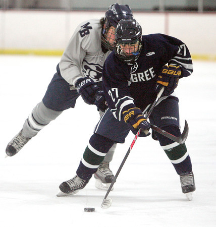Ken Yuszkus/Staff photo. Hamilton: Pingree's Zachery Mitchell has a Moses Brown player trying to reach for the puck with his hockey stick during the Moses Brown School at Pingree hockey opener.