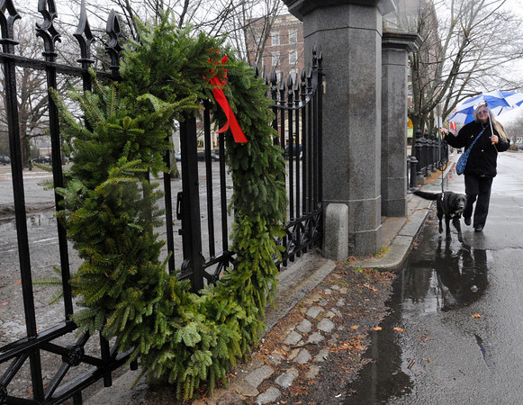 Ken Yuszkus/Staff photo. With umbrella in hand to fight the rain, Kim Eno walks her dog Nama at Salem Common near the large wreath that is at the entrance of the park.