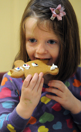 Ken Yuszkus/Staff photo. Wenham:<br /> Gracelyn Skillings, 5, of Somerville, eats her gingerbread cookie which she decorated at the Wenham Museum.