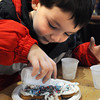 Ken Yuszkus/Staff photo. Wenham:<br /> Anthony Hartford, 4, of Ipswich, finishes decorating his gingerbread cookie by pouring colored sugar crystals on it at the Wenham Museum.