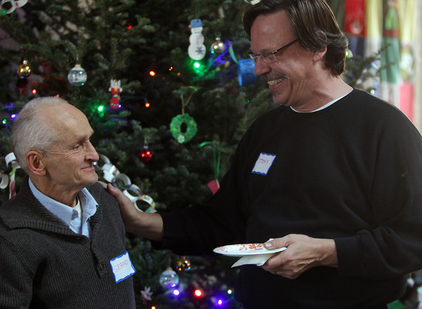 Danvers: Tony Toledo, right, of Beverly, talks with Gerard Sevigny in front of the Christmas tree at the 32nd annual Christmas Dinner with Friends held at the North Shore Unitarian Universalist Church in Danvers on Wednesday afternoon. DAVID LE/Staff Photo