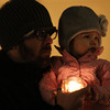 Jon Paddol, of Beverly, and his daughter Pai, 2, hold a candle during an impromtu vigil held at the flagpole on Beverly Common on Friday evening to remember the victims from the Connecticut school shooting earlier Friday morning. David Le/Staff Photo