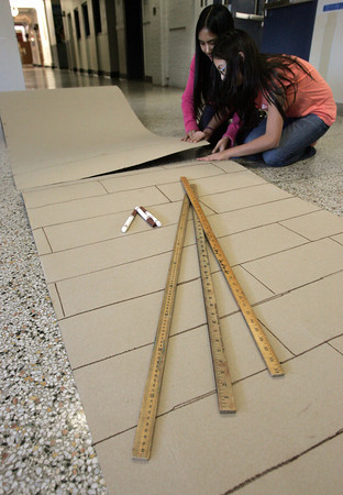 """Salem:<br /> Abby Carino, left, and Sophia Kapoglis, both 6th graders, tape together rolls of cardboard which will be a boardwalk for the Collins Middle School's """"a night at the beach"""" fundraiser <br /> Photo by Ken Yuszkus/The Salem News, Monday, December 3, 2012."""