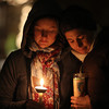Brittany Schimpf, left, and Heather Gallant, both of Beverly huddle together during an impromtu candle light vigil to remember the victims of the shooting in CT on Friday evening at Beverly Common. David Le/Staff Photo