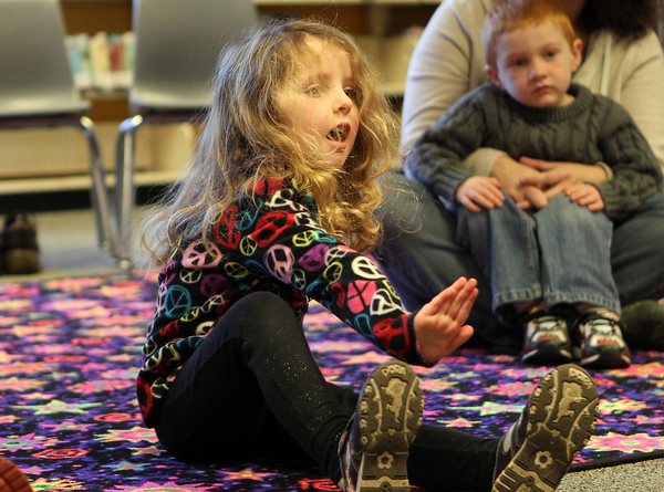 """Maura Shinnick, 4 1/2, of Salem, sings along to """"Frosty the Snowman"""" at a Holiday Sing-a-long at Peabody Public Library on Saturday morning. David Le/Staff Photo"""
