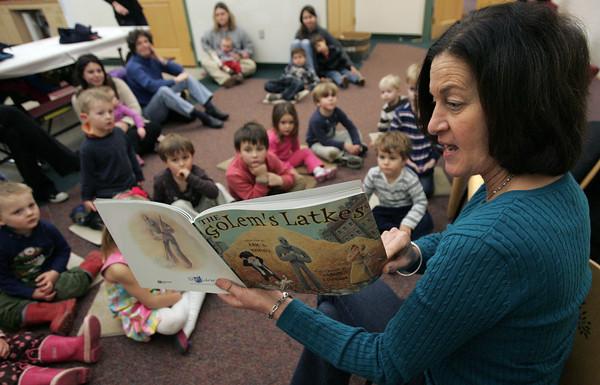 "Hamilton:<br /> Debbie Coltin reads ""The Golem's Latkes"" at the start of the Hanukkah party at the Hamilton-Wenham Public Library.<br /> Photo by Ken Yuszkus/The Salem News, Tuesday, December 11, 2012."