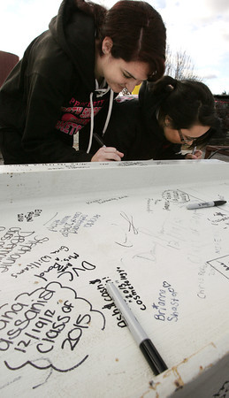 Middleton:<br /> North Shore Technical High seniors Kayla Doig of Beverly, left, and Adrianna Mirabile of Salem, sign their names on a steel beam to be used in the new $133 million technical and agricultural school in Danvers. <br /> Photo by Ken Yuszkus/The Salem News, Wednesday, December 19, 2012.
