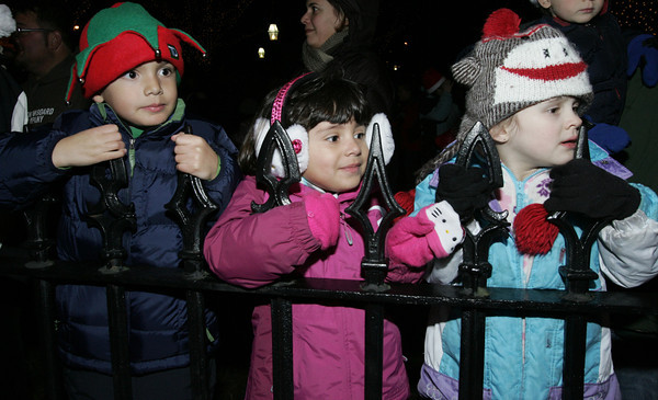 Salem:<br /> From left, twins Adam and Samantha Sparacio, 5, and Olivia Loux, 5, wait for Santa to descend from the roof of the Hawthorne Hotel by ladder courtesy of the fire department.<br /> Photo by Ken Yuszkus/The Salem News, Friday, December 7, 2012.