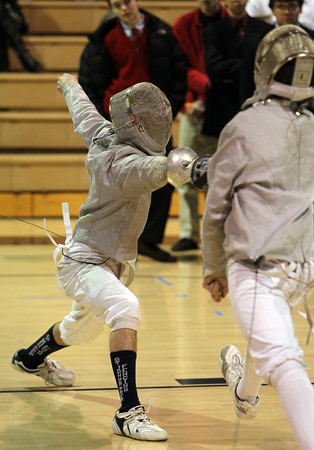 St. John's Prep fencer Colin MacGregor, left, lunges forward and pokes his opponent to gain a point on Thursday evening. David Le/Staff Photo