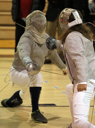 St. John's Prep fencer Ethan Smith, left, exchanges blows with his Concord-Carlisle opponent on Thursday evening. David Le/Staff Photo