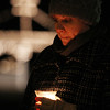 Amanda Gaines, of Salem, bows her head while holding a candle at an impromtu vigil on Beverly Common to remember the victims of the school shooting in Connecticut. David Le/Staff Photo